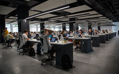 Large room with many desks, workers at computers